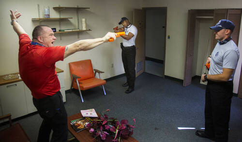 One man wildly points a red training gun in the direction of another man.