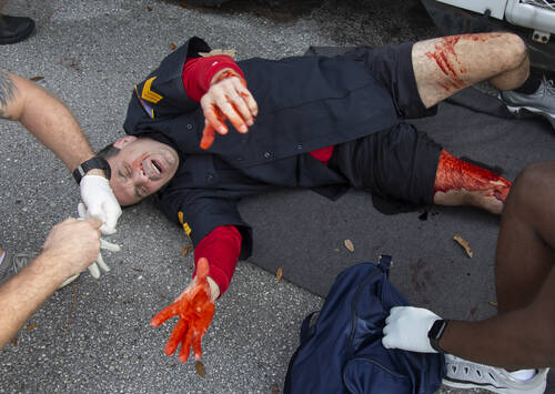 A man covered in fake blood lies on the ground as someone in the foreground pulls on latex gloves.