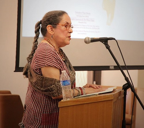 Photo from a poetry reading event with Rosemary Catalos. Ms. Catacalos is standing at a podium with a microphone.