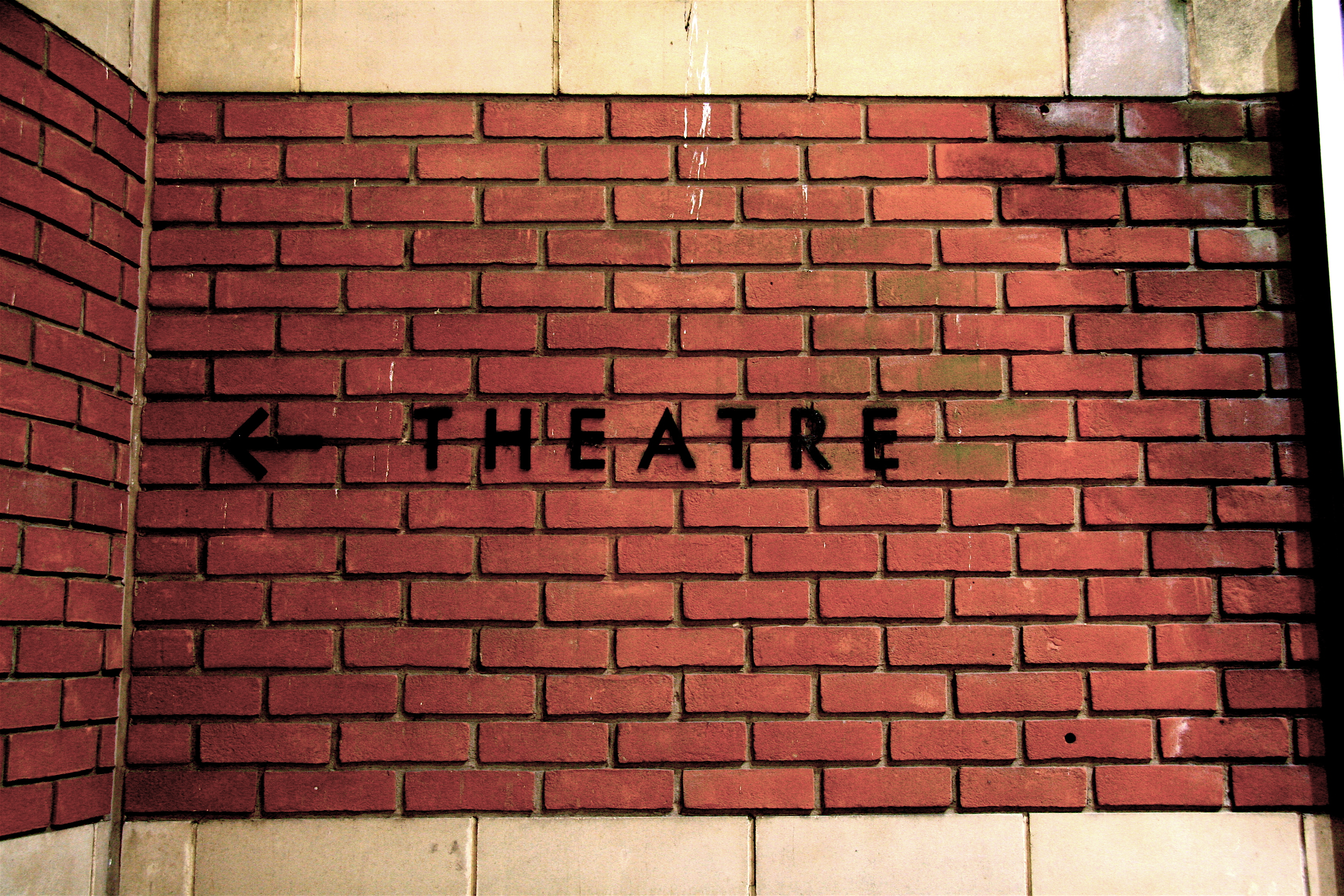 """Theatre"" sign on brick wall"
