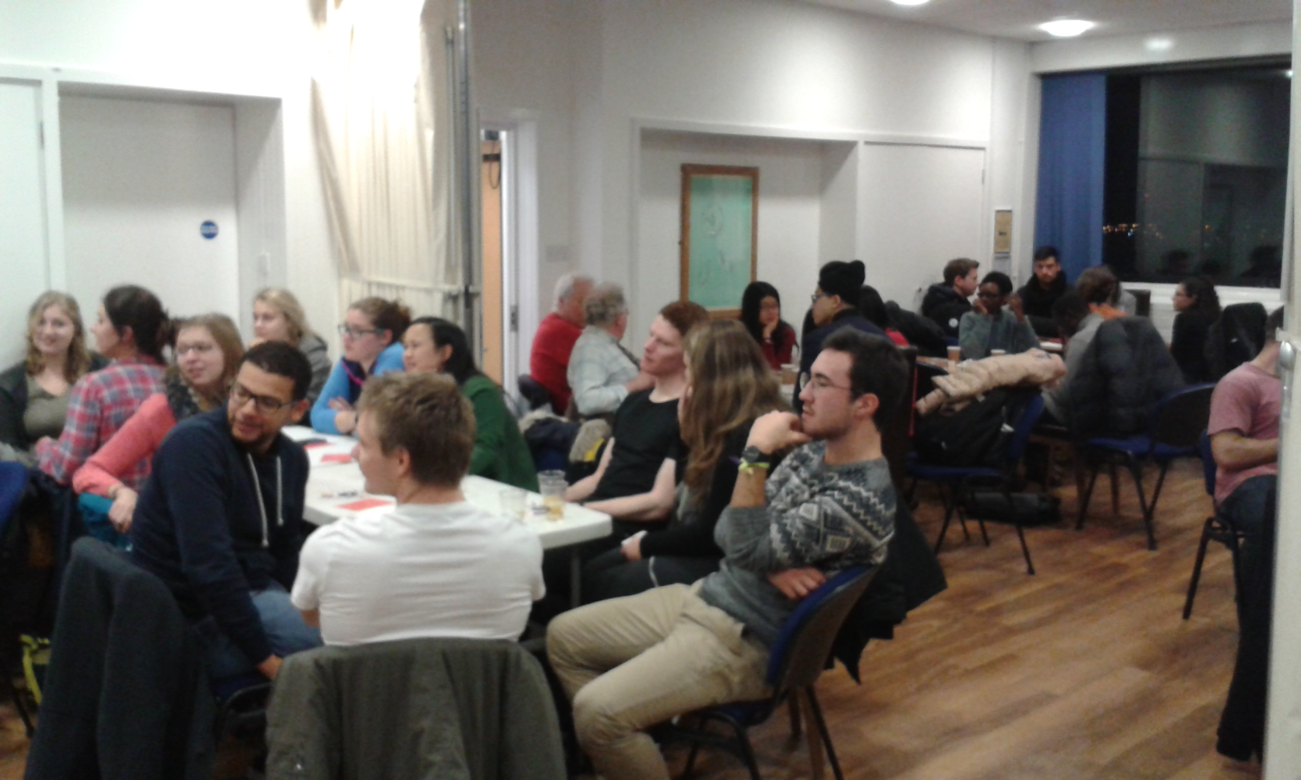students seated at tables at a welcome event university of dundee