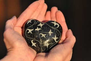 cupped hands holding decorated stone heart