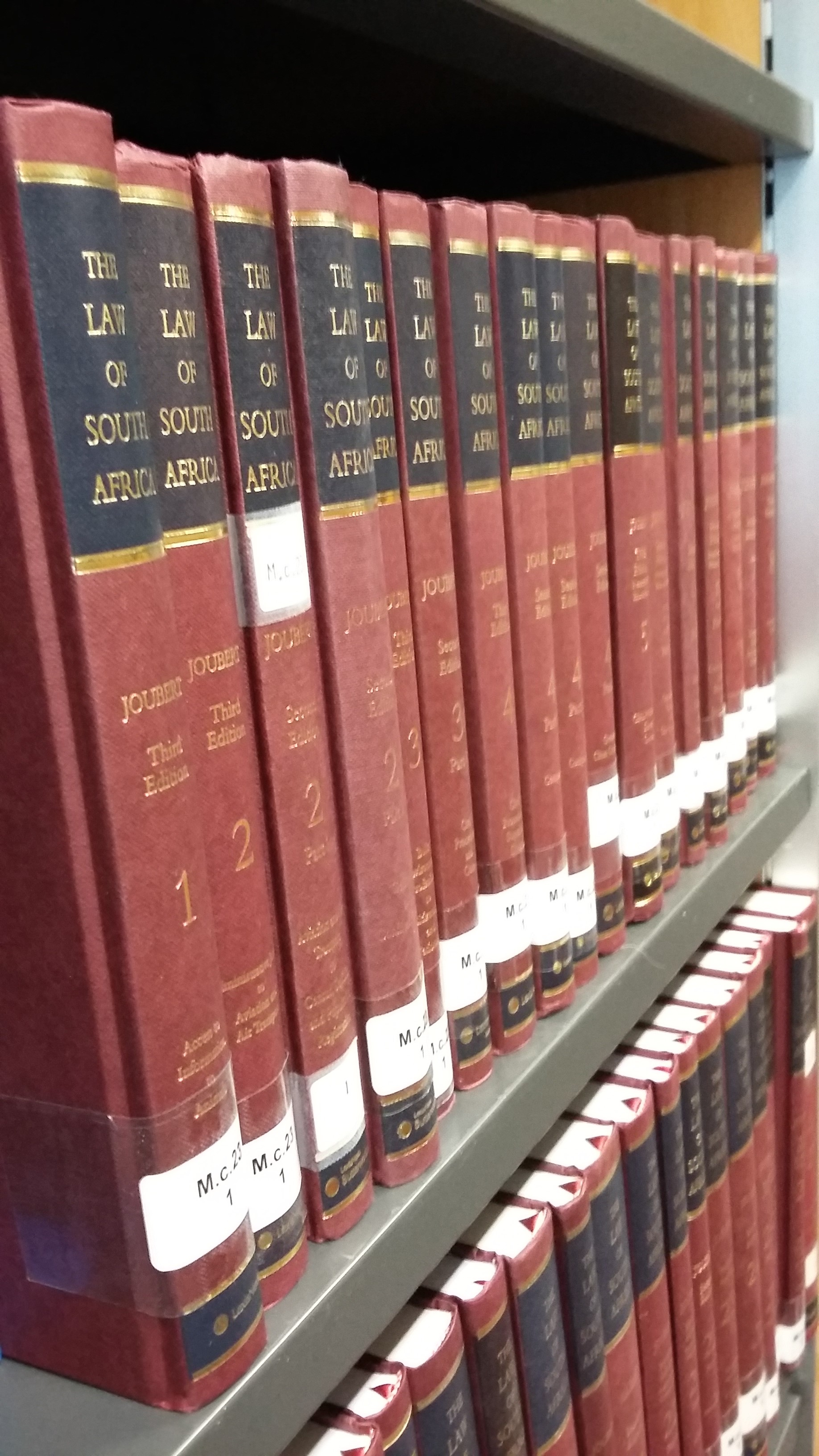 Photo of the red and black volumes with gold lettering of the Law of South Africa on shelves in the Squire Law Library.