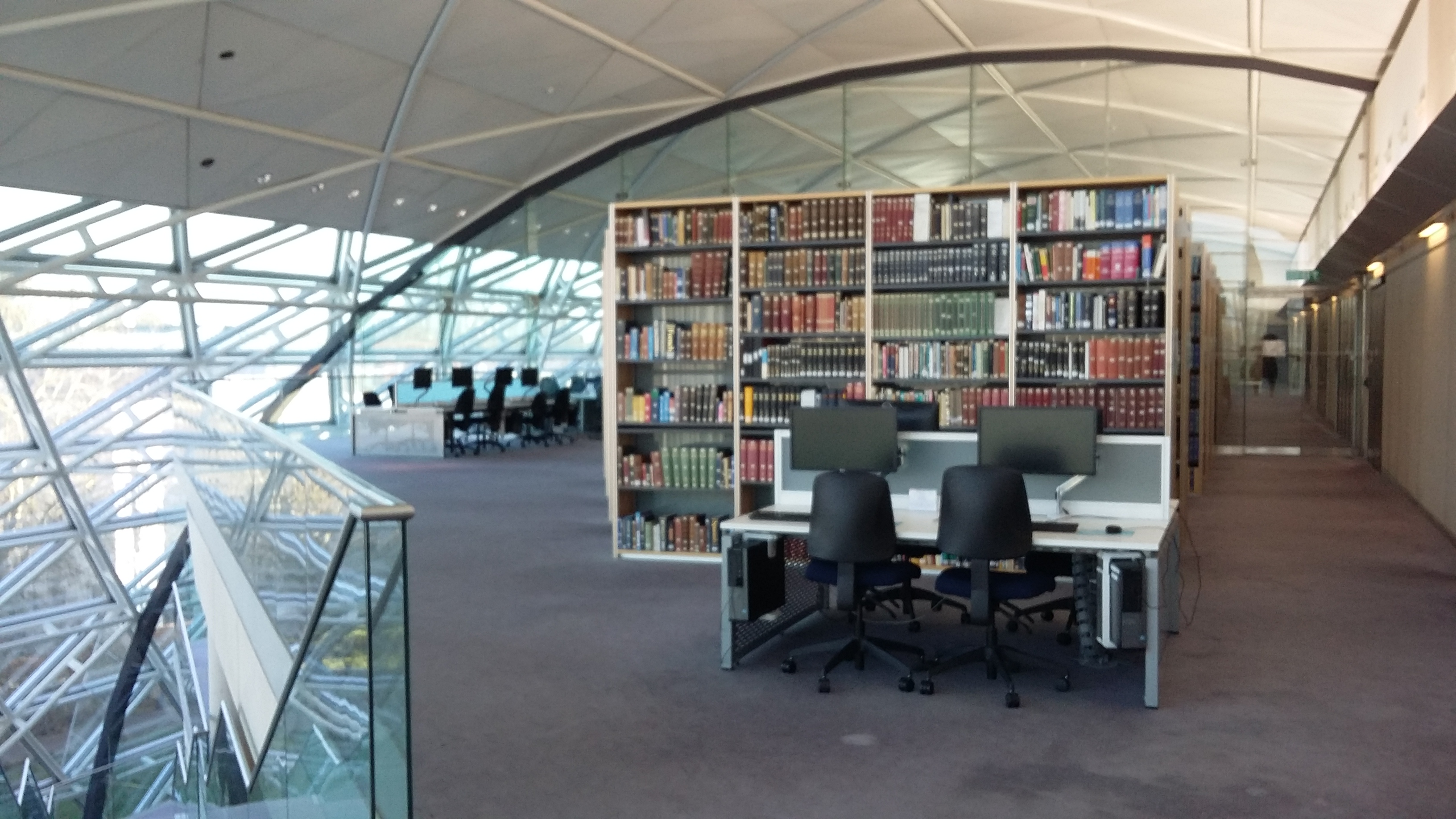 Picture of the third floor of the Squire Law Library with books and computers and a stunning building designed by Foster and partners.