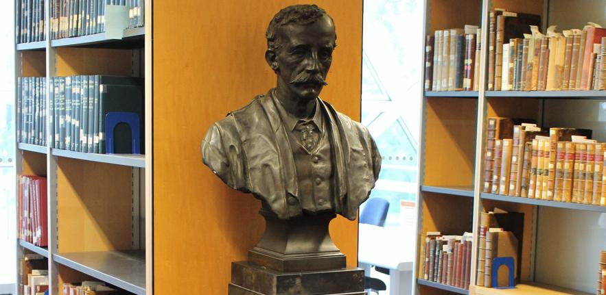 Photo of a bust of Frederic Maitland surrounded by rare books in the Maitland Legal History Room of the Squire Law Library.