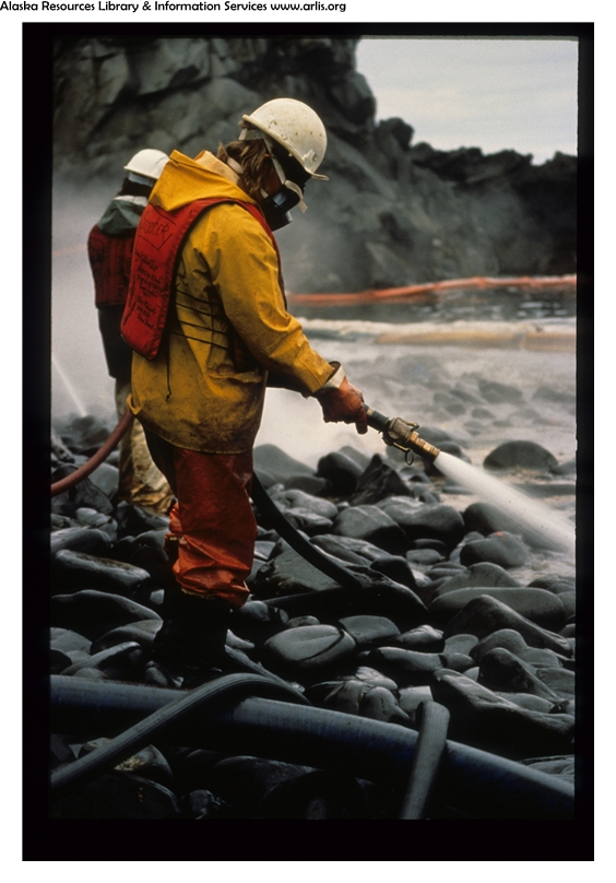 A worker uses a hose to wash oil from coastal rocks, follwoing the Exxon Valdez oil spill.