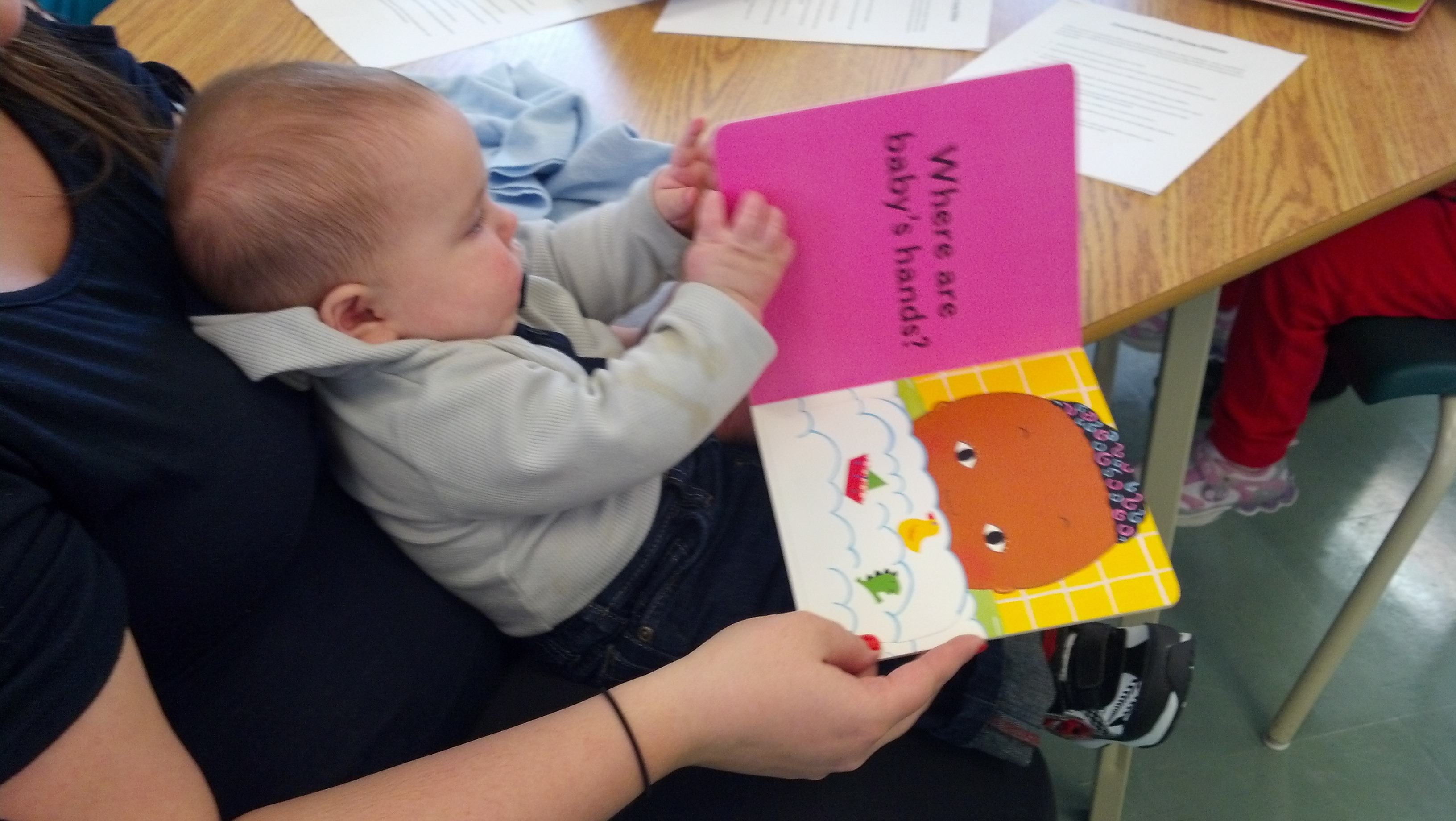 infant reading a board book with caregiver