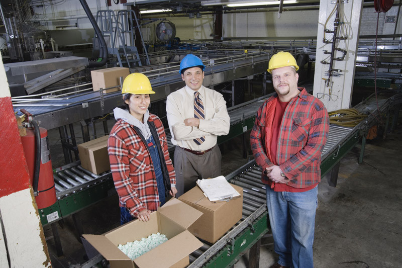 Image of three people in warehouse looking at camera