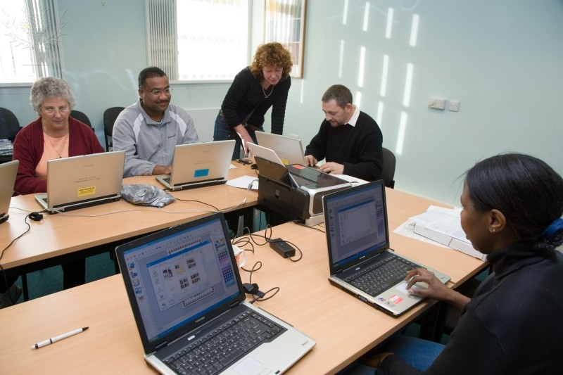 Image of people working on laptops with an instructor