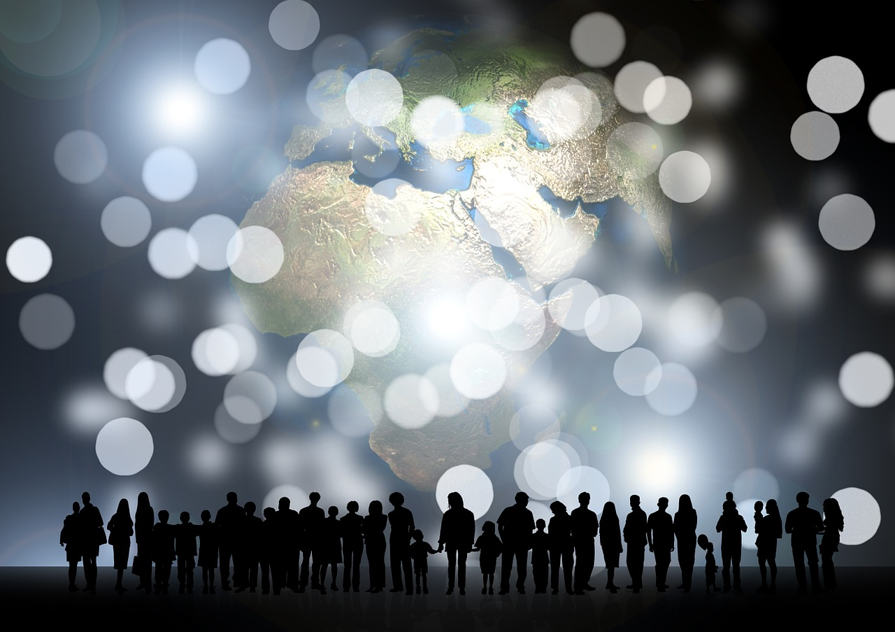 A silhouette of a group of people against a world map background.