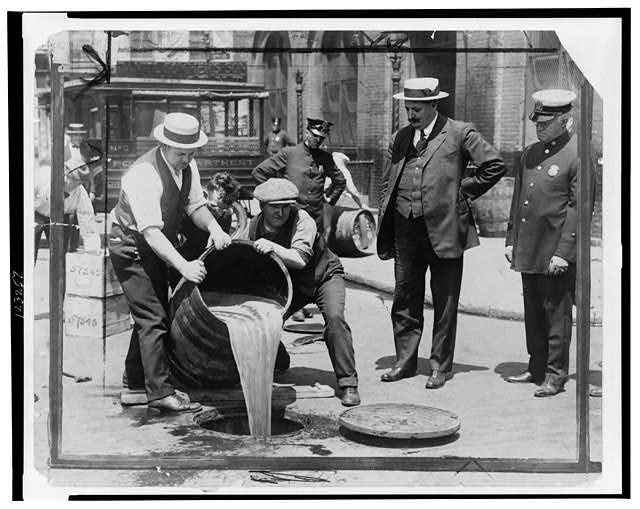 Men dumping alcohol into sewer during Temperance era