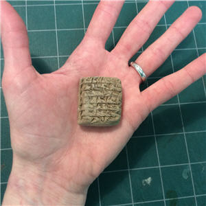 Hand holding cuneiform clay tablet