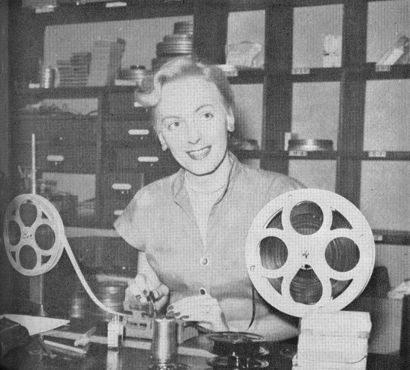 Christine Jorgensen sitting in a photo lab editing film.