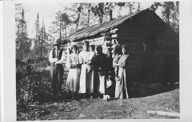 Ojibwe family in front of log home, approx. 1915