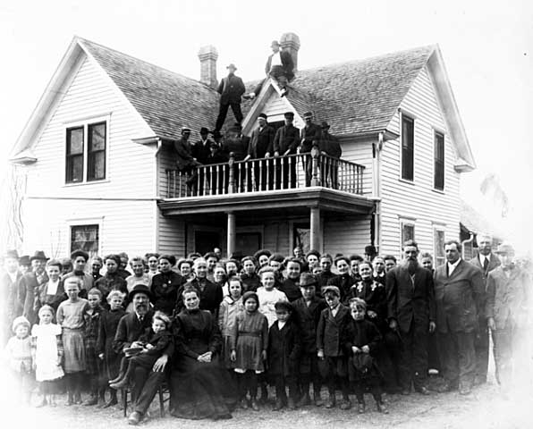 Group portrait in front of house, family reunion, Chippewa County, approx. 1900