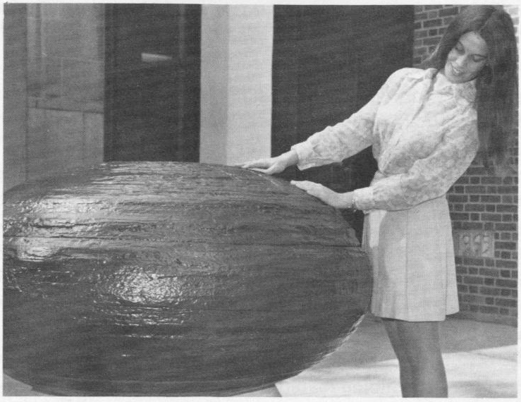 Debbie Danko standing beside the concretion looking intently at it outside Deike building