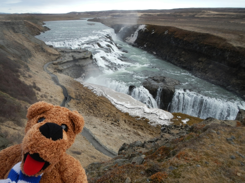 a waterfall through barren land with a Nittany Lion stuffed animal in the foreground