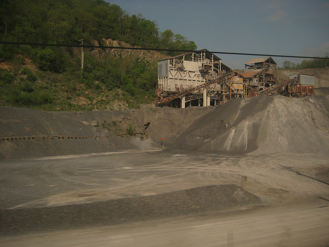 photo showing a stone quarry with a building in the background and small particle stone in the foreground