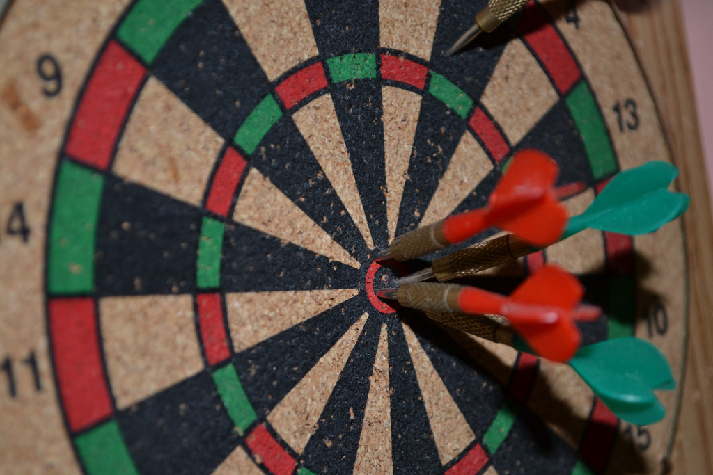 Dart board with several darts in the bulleye