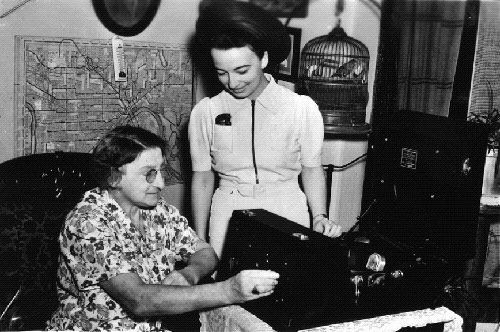 WPA volunteer demonstrates a talking book to a blind woman