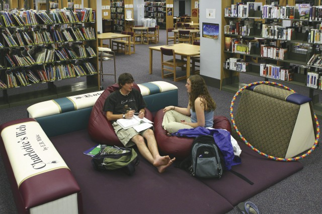 students sitting in library in front of DVDs.