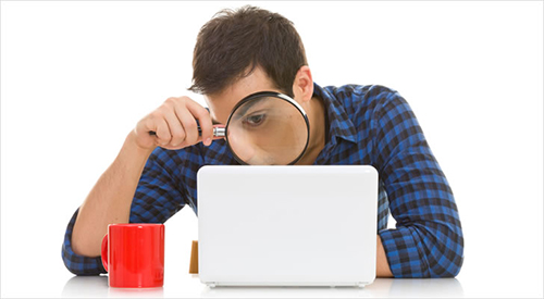 young man looking at a computer through a magnifying glass trying to find something