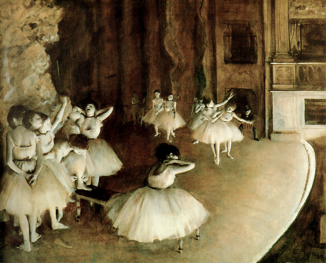 Edgar Degas painting of ballet dancers warming up on stage.