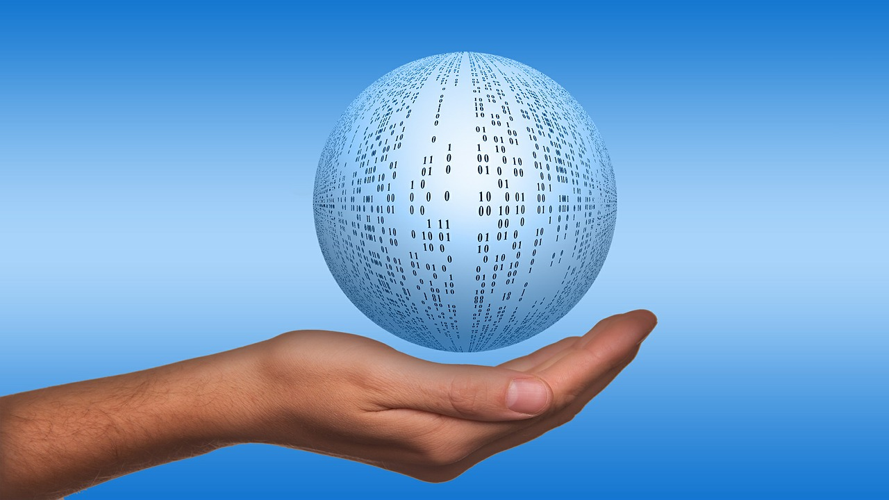 Image of a person's hand holding a light blue and white sphere with 1s and 0s on it in black type - representing data (on a medium blue background)