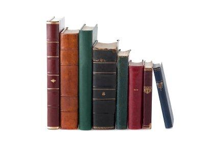 A picture of eight books of different sizes and shapes lined up next to each other.