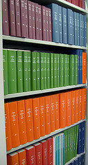 A shelf showing many rows of journal volumes in different colours.