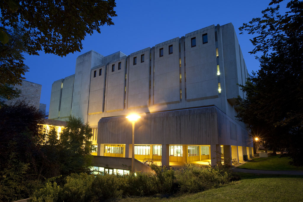 Image of the exterior of the Murray Library in the summer, as seen from the Aboriginal Student Centre. It is night and the lights from the library are glowing brightly.