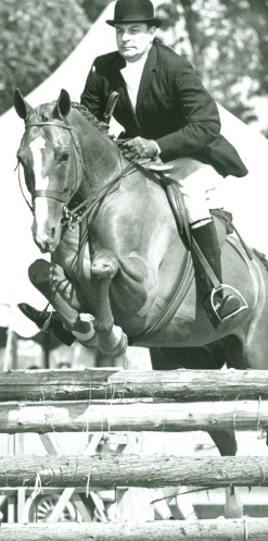 Peter Vanderhoef atop horse jumping fence.