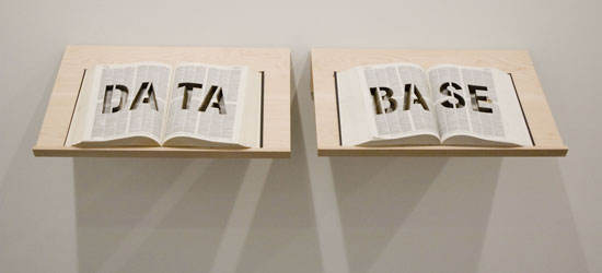 An image of a sculpture with two books on stands with the words data and base carved out of the pages