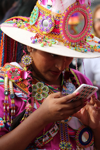 Woman in festive Chilean clothing looking at her cell phone