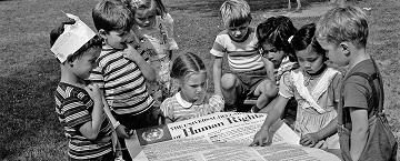 picture of children looking at the Declaration of Human  Rights in 1950