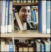 Male student standing behind bookshelf and peering through an open space with books on either side.