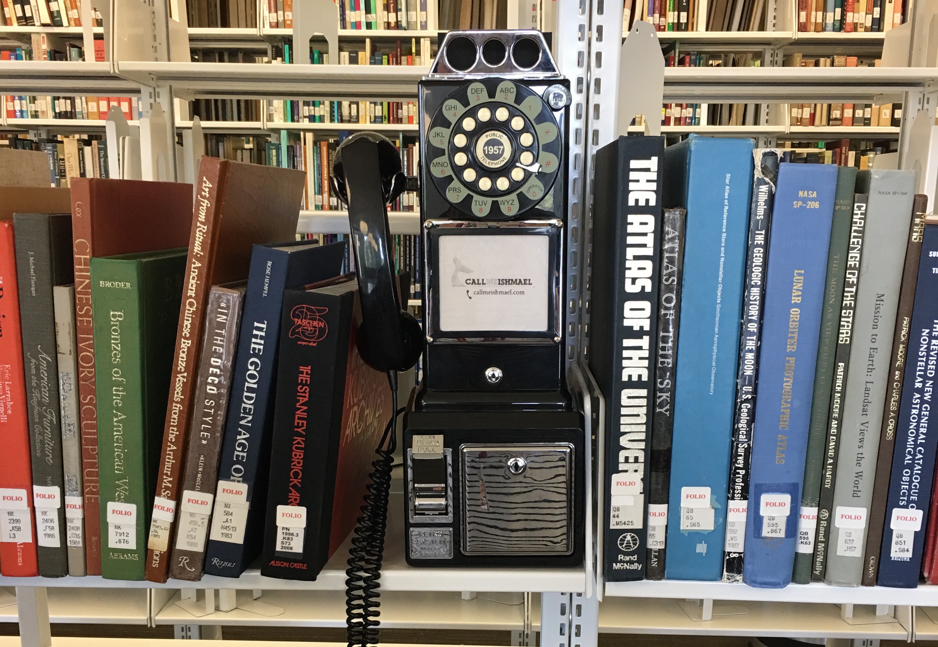 "Image of a faux-rotary style phone on a library bookshelf. The phone has the words, ""Call me Ishmael"" on it"