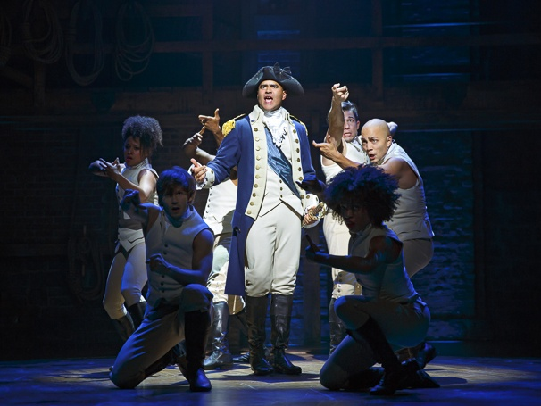 Image of Hamilton cast: Washington surrounded by dancers pretending to shoot guns