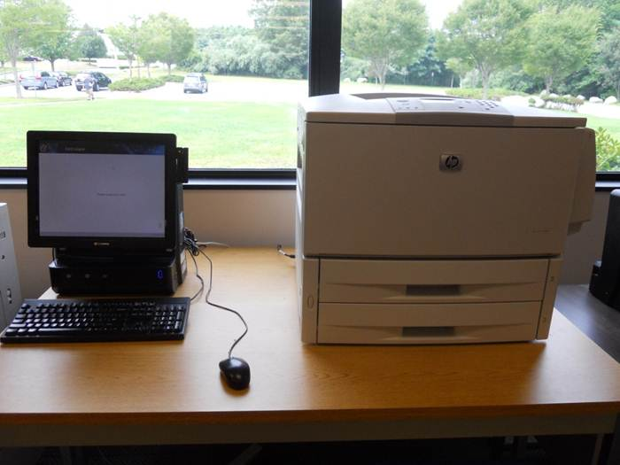 Photo of a computer next to a printer.