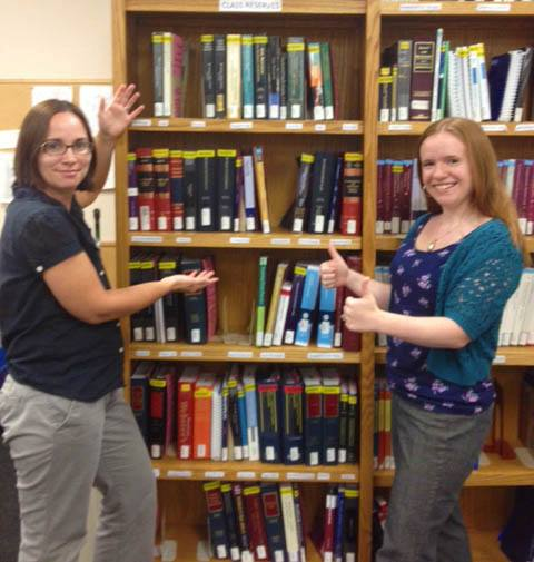 Photo of law librarians, Jessica and Emma, standing in front of the reserves shelf.