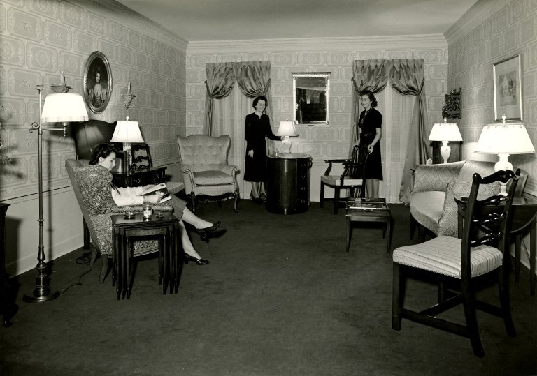 This black and white photo shows women sitting in a room together.