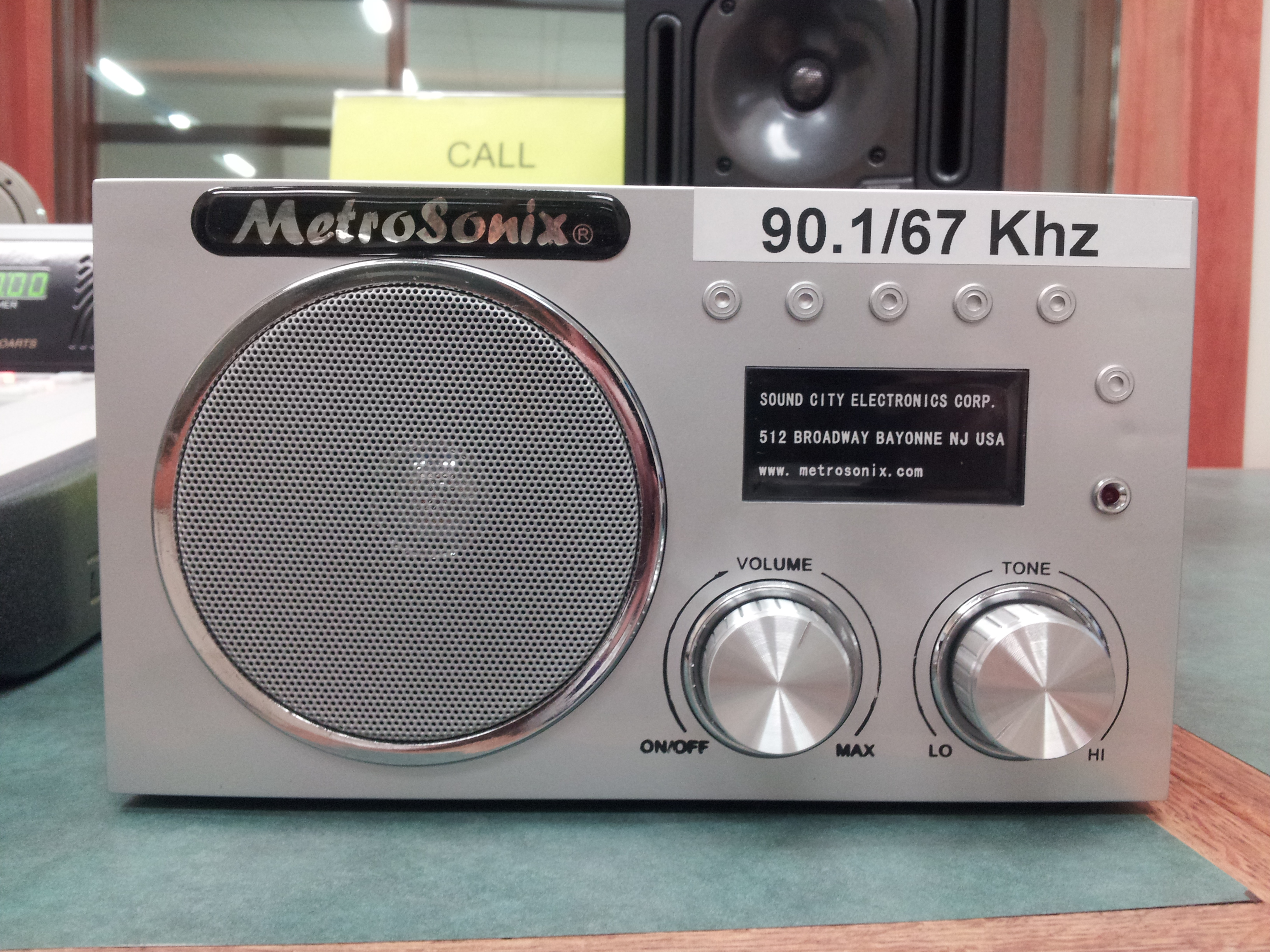 Gray metal radio, Metrosonix brand, large round speaker on the left, 2 small knobs on the bottom right