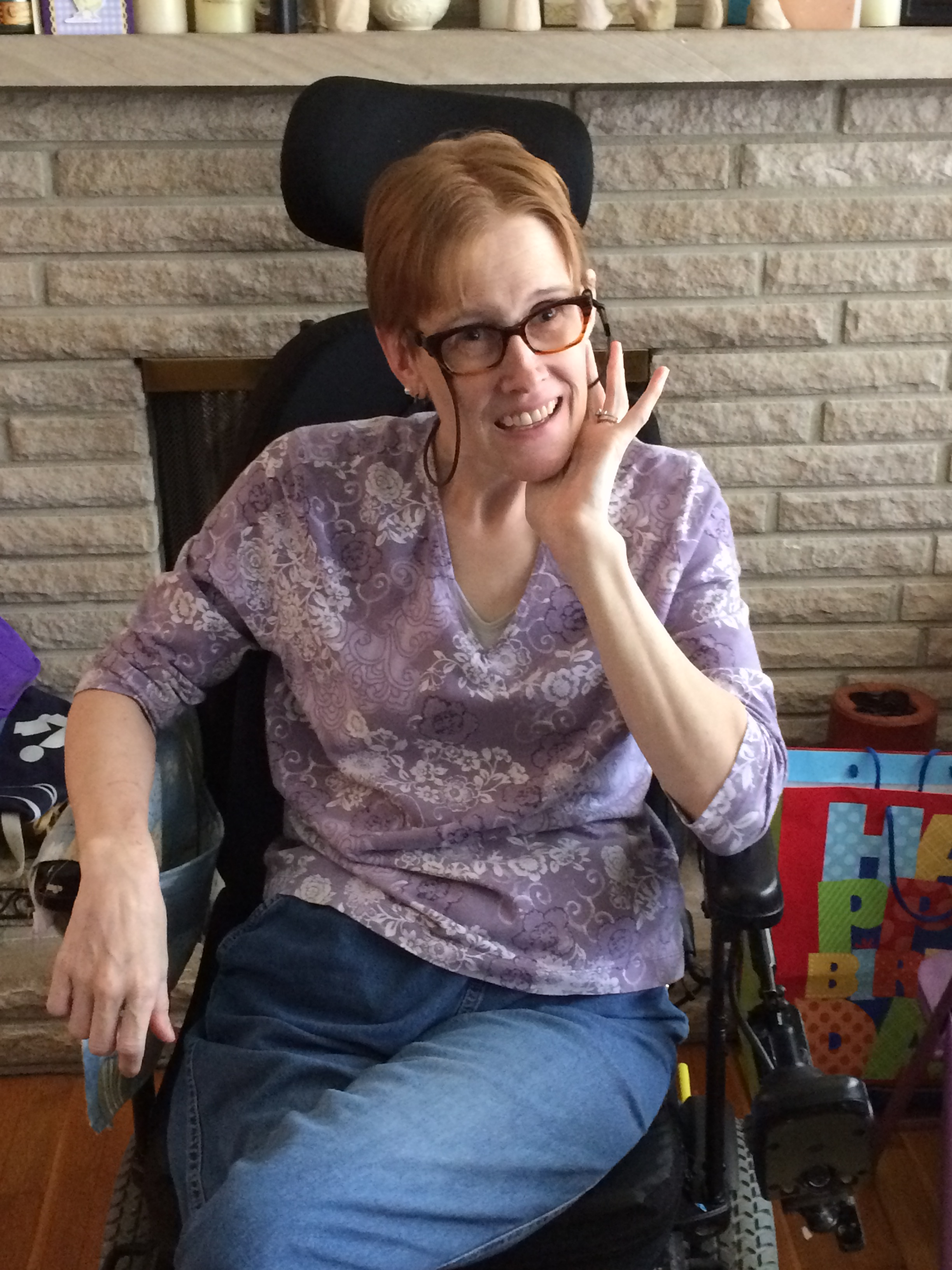 Redheaded lady sitting in a wheelchair, wearing a purple shirt and jeans.