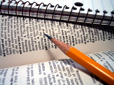 Image of a pencil and notebook lain across a dictionary with the word 'education' and its meaning