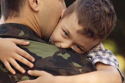 Father in camouflage uniform hugging child.