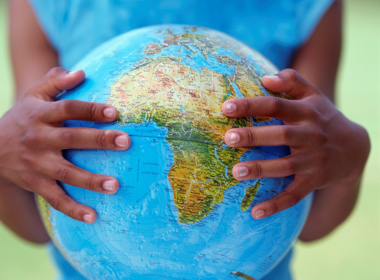 Photo of hands holding a globe.