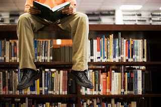 young man sitting on top of bookshelf reading