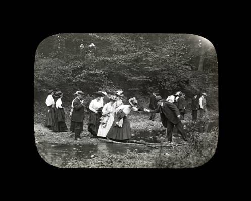 Men and women cross a stream circa 1900. The scene is located near present-day Golf Road and the Chicago River.