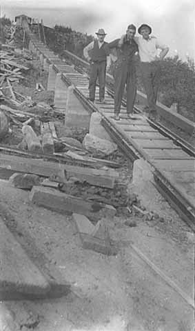 Trio of men (left to right: Keeper Pete Young, ?, Conrad Lovutson) on lower tramway during construction (1916)
