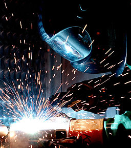 welder in helmet with sparks flying